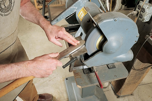 Grinding is the easiest way to raise a burr. With a grinding rest set at 15 ˚ to 25˚, start moving the scraper edge as soon as it touches the wheel.