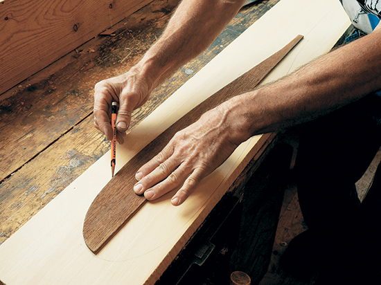 "Mark the center of the board's growth ring pattern on the end of the board. Then draw a centerline on the wide face. Determine how long your paddle will be and mark the top and bottom ends of the paddle on the centerline. Then trace the blade and handle (inset photo) patterns on both sides of the centerline. Measure 9/16"" out on either side of the centerline and draw lines to designate the 11⁄8""-thick shaft between the blade and handle. Next, use a band saw to cut out the paddle shape."